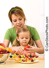 Woman and little girl slicing fruits