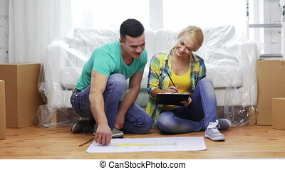 smiling couple looking at blueprint in new home - moving,...