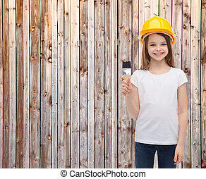smiling little girl in helmet with paint roller -...