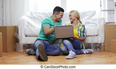 couple with laptop sitting on floor in new house - moving,...
