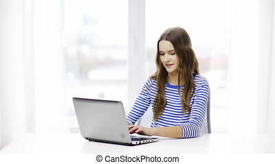 smiling teenage girl with laptop computer at home - home,...