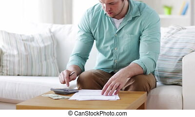 man with calculator, papers and money at home - savings,...