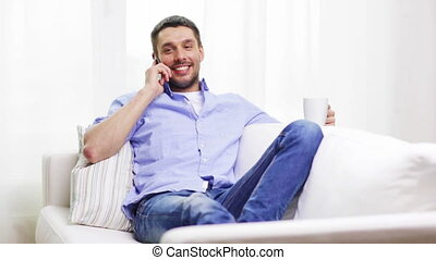 laughing man with smartphone at home