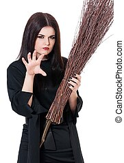 Young witch with broom concentrated on a spell isolated on...