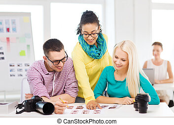 smiling team with printed photos working in office -...