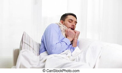 ill man with flu at home sneezing and blowing nose - home,...