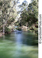 Jordan River, Israel - The calm waters of the Jordan River...