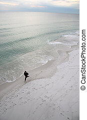 Man Running By The Seashore - A lone man runs along the...