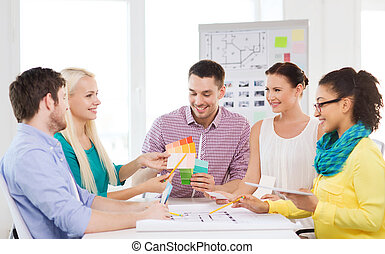 smiling interior designers working in office - technology,...