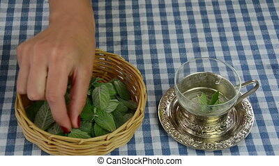 mint tea prepare - Hand put mint plant leaves from wicker...
