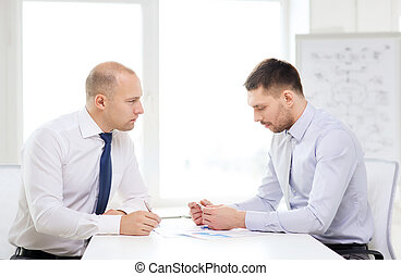 two serious businessman with papers in office - business and...