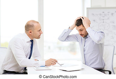 two serious businessmen with tablet pc in office - business,...