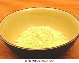 Cornmeal  in a bowl of ceramic on an orange background