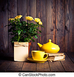 yellow roses in pot, t?apot, tea cup and old books on wooden...