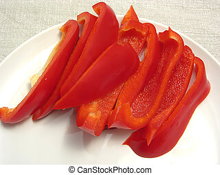 Slitted red pepper on a white plate and placemat