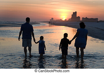 Young Family Silhouetted By Sunset - A young family with...