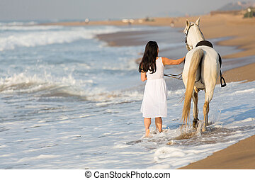 rear view of young woman walking a horse on beach - rear...