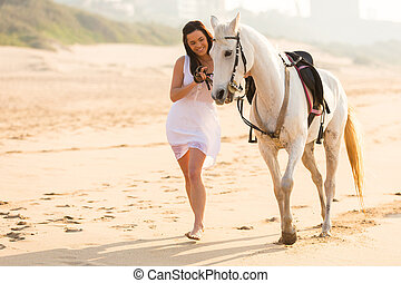 cheerful young woman walking with a horse on beach in early...