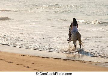 young lady horse ride on beach - back view of young lady...