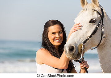 happy woman comforting her horse on beach