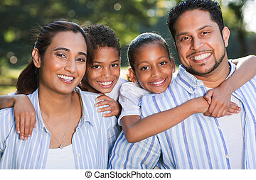 indian family having fun together outdoors - portrait of...