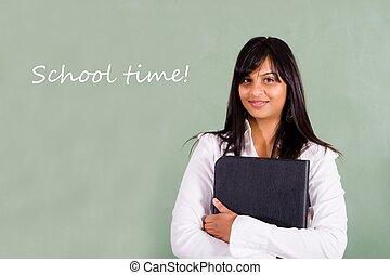 school teacher in front of her blackboard