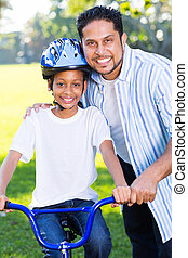 young indian girl on a bike with her father standing next to...