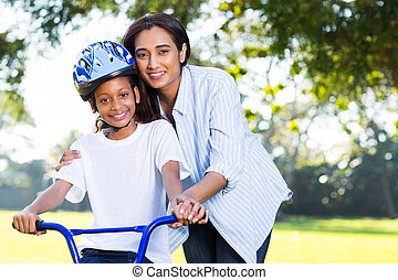 indian mother teaching her daughter to ride a bike