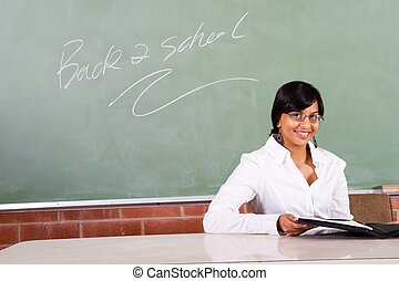 lovely teacher - beautiful indian woman at her desk in...