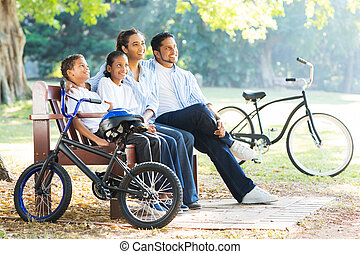 indian family relaxing in the park - modern indian family...