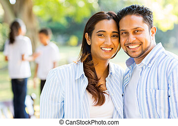 happy indian couple standing in front of their children -...