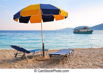 Colorful sun umbrella and two sunbeds with a blue sea and a boat