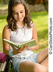 Student girl reading book in park summer