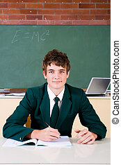 teen student - schoolboy at his desk with textbooks