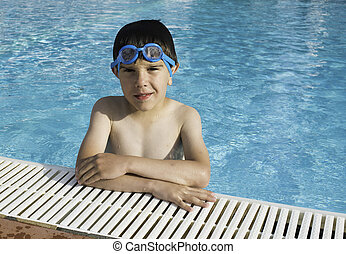 Child in swiming pool. Blue glasses