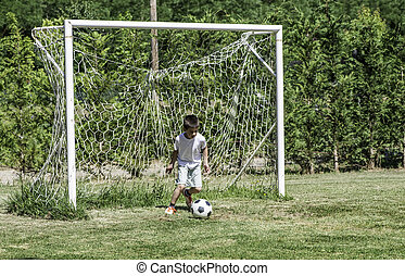 Child playing football in a stadium. Trees on the background