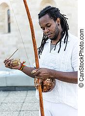 African Capoeira Rastaman,playing a instrument berimbau