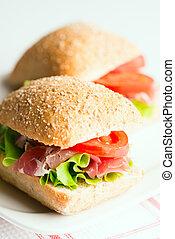 Prosciutto sandwiches with tomato and arugula on table