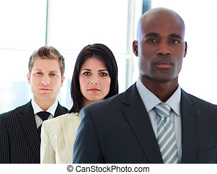Serious businesswoman in focus with her team in a line -...