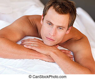 Young man lying in bed - Isolated young man lying in bed