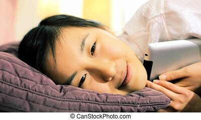 Falling asleep hugging ipad - Happy asian girl falling...