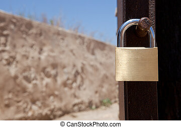 Country house padlock - New pad lock hanging on a rusty...