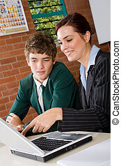 teacher and student using laptop together