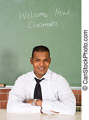 indian male teacher - handsome indian teacher sitting behind...