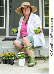 Happy elderly lady ready to transplant her flowers sitting...
