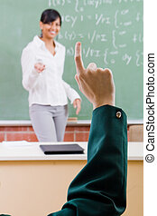 maths lesson - a student answerting a question by lifting up...