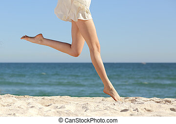 Beautiful woman long legs jumping on the beach with the sea...