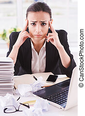 Tired businesswoman. Young business woman holding head in hands and looking at camera while sitting at her working place