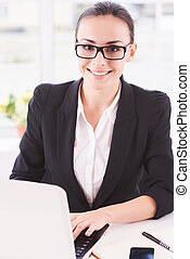 Businesswoman at work. Young business woman using computer and smiling while sitting at her working place