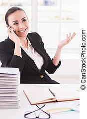 Happy businesswoman. Happy young woman in formalwear talking on the mobile phone while sitting at her working place